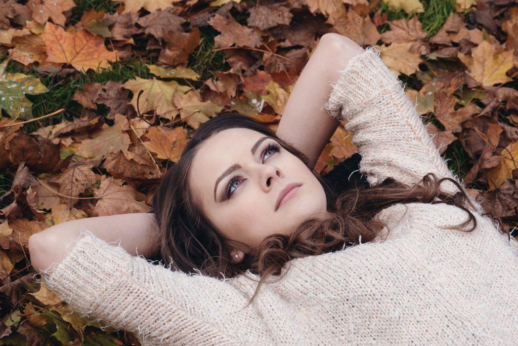 Junge Frau nachdenklich im Laub